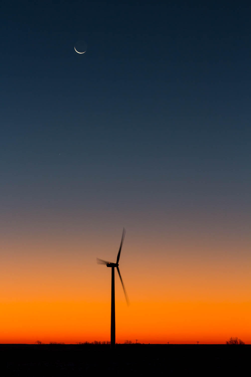 a wind turbine set against the morning sky with a crescent moon at the top of the frame