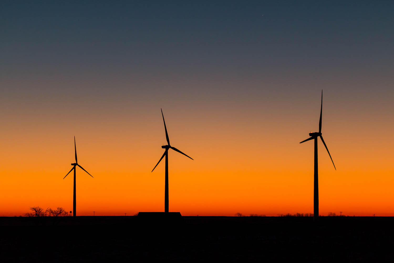 three wind turbines silhouetted against a setting sun