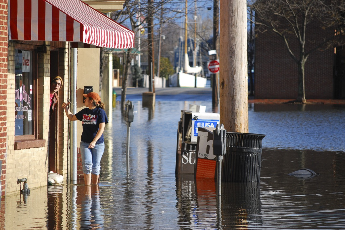 a street is flooded up to a woman's shin. she has her jeans rolled up and is waving to a man who is sticking his head out a door that is barricaded with sandbags.