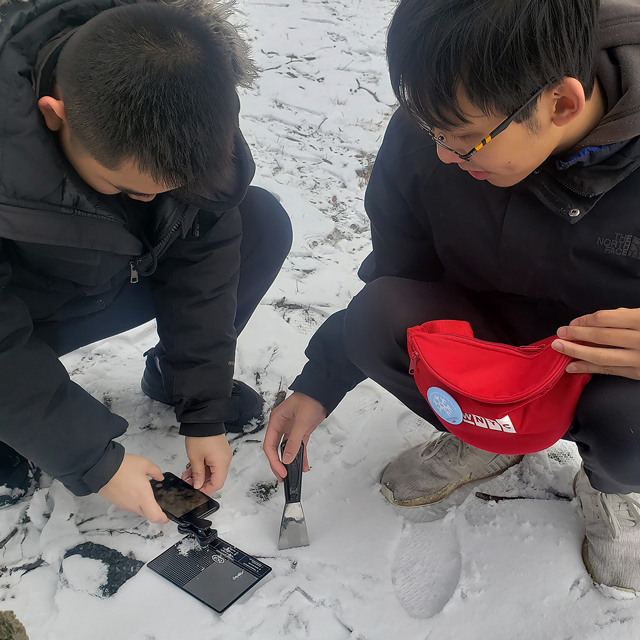 two students crouch on the snow-covered ground with the instruments from the fanny pack and inspect the snow