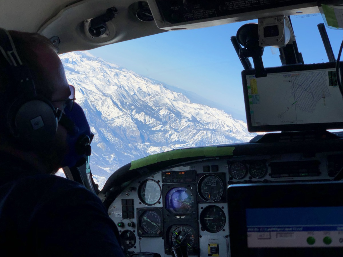 inside view of a person in an airplane observing snowpack from the window