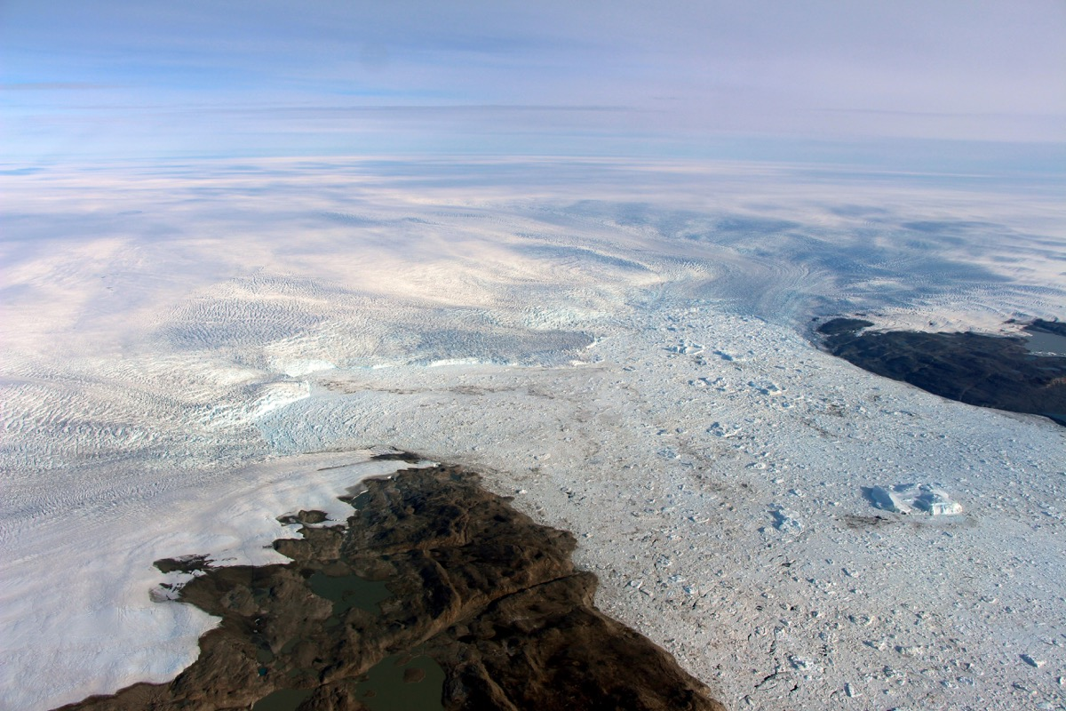 the edge of a glacier as seen from the air, which is releasing icebergs into the ocean.
