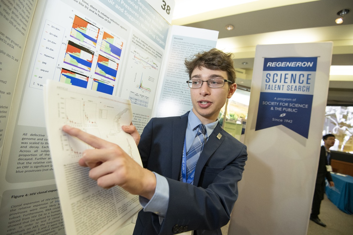 a boy stands in front of a poster board display and points to a piece of paper