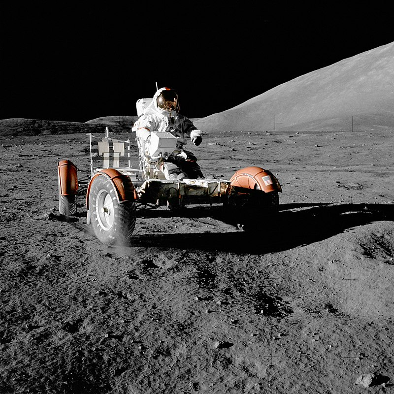 person in space suit riding a vehicle across the rocky gray surface of the moon against black sky