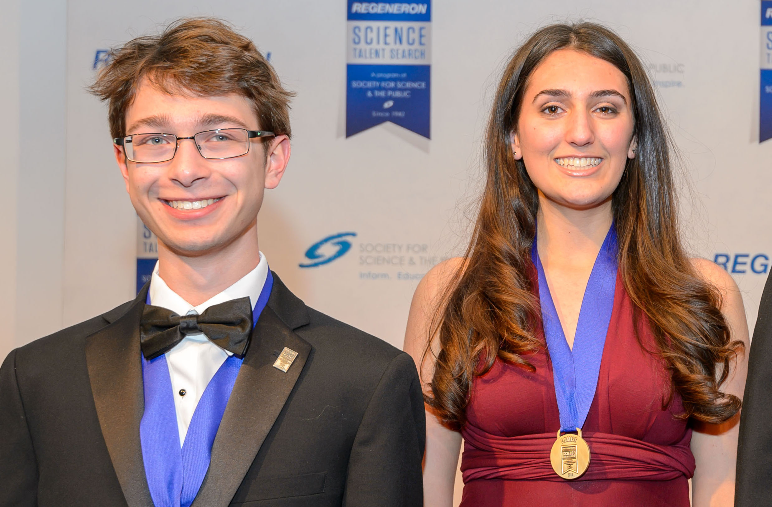 teenage boy with blond hair and wearing a bow tie standing next to teenage girl with long brown hair and red dress. both are wearing medals around their neck and smiking