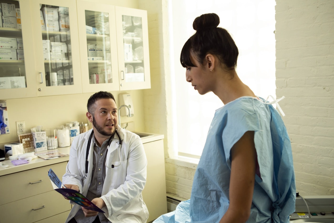 A patient in a hospital gown speaking to her doctor in an exam room.