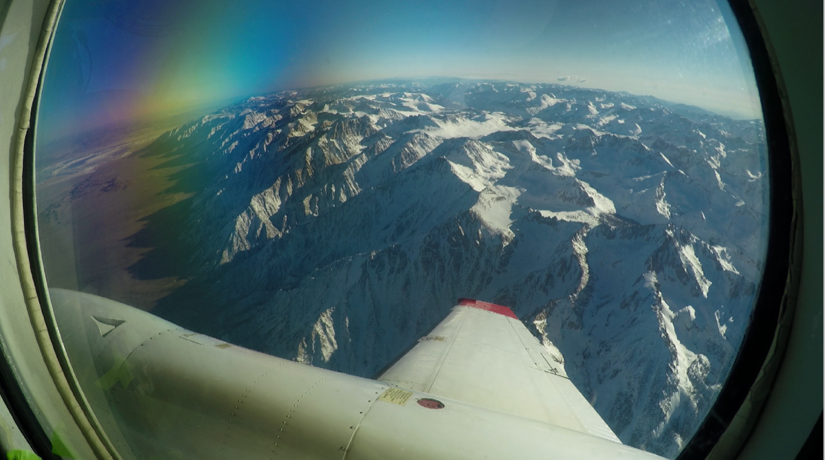 view out the window of a plane wing observing snow on mountains