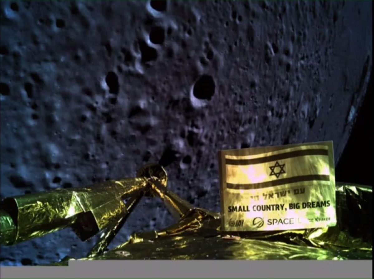 "at the bottom of the image is the golden top of the beresheet lunar lander. in the background is the looming, cratered lunar surface. in the foreground of the camera, mounted on the lander, is a small golden sign that features the israeli flag and the words ""Small Country Big Dreams"" in both English and Hebrew"