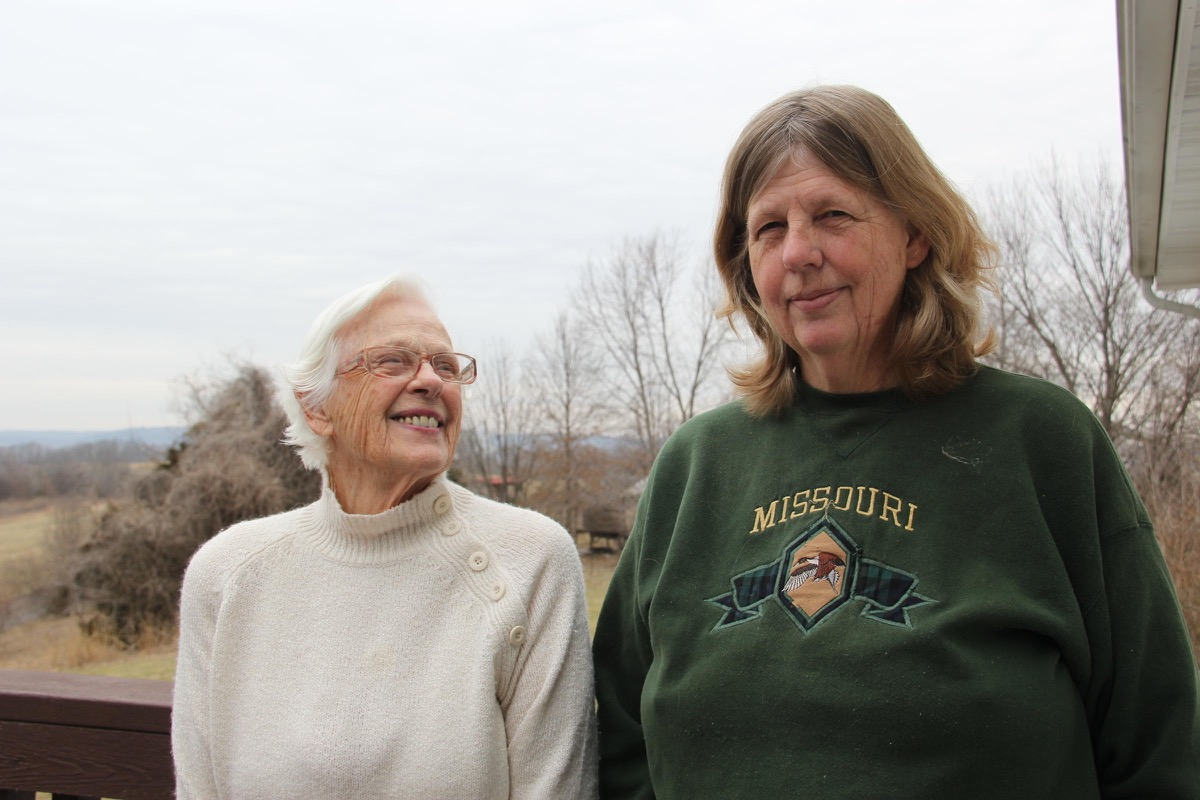 "two women, one with white hair and glasses and another wearing a ""missouri"" sweater"