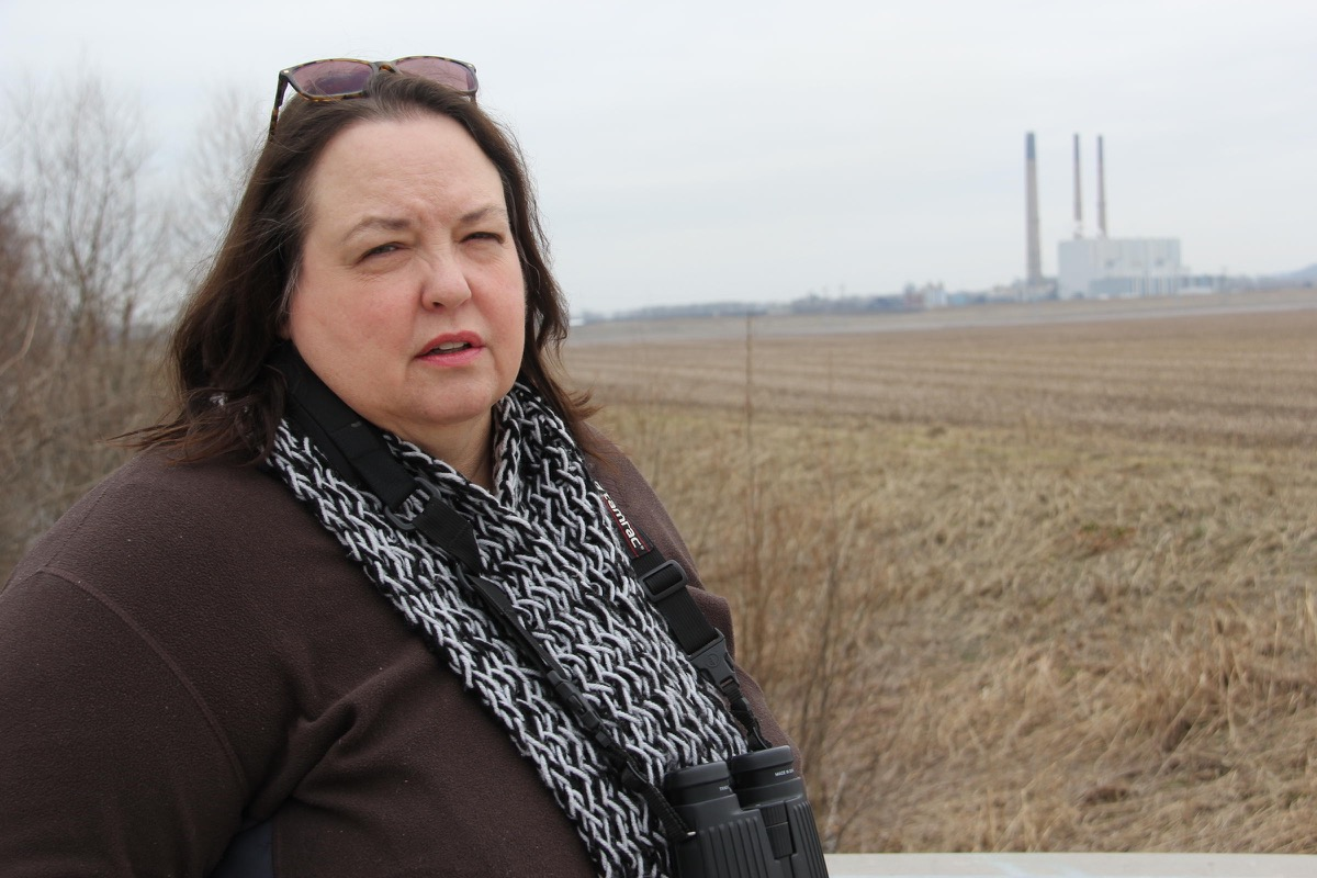 schuba stands in a field with a coal plant in the background, wearing sunglasses and binoculars around her neck