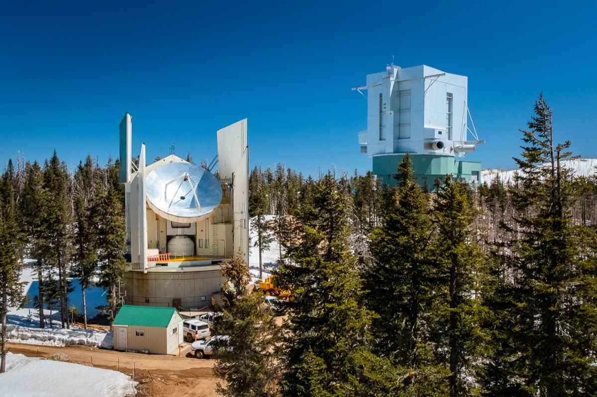 a radio dish out in the middle of a foresty mountain side covered in snow under a clear blue day