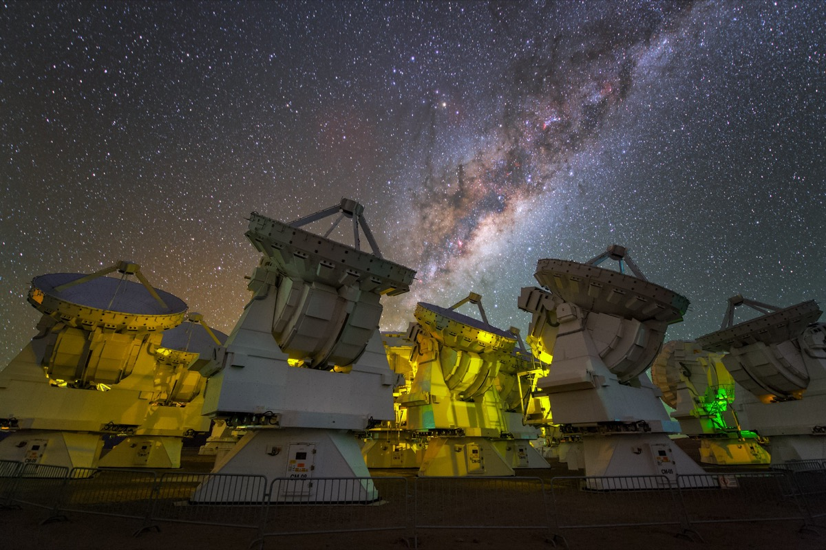several radio dishes that are glowing softly under green-ish light. above is the night sky and the milky way galaxy
