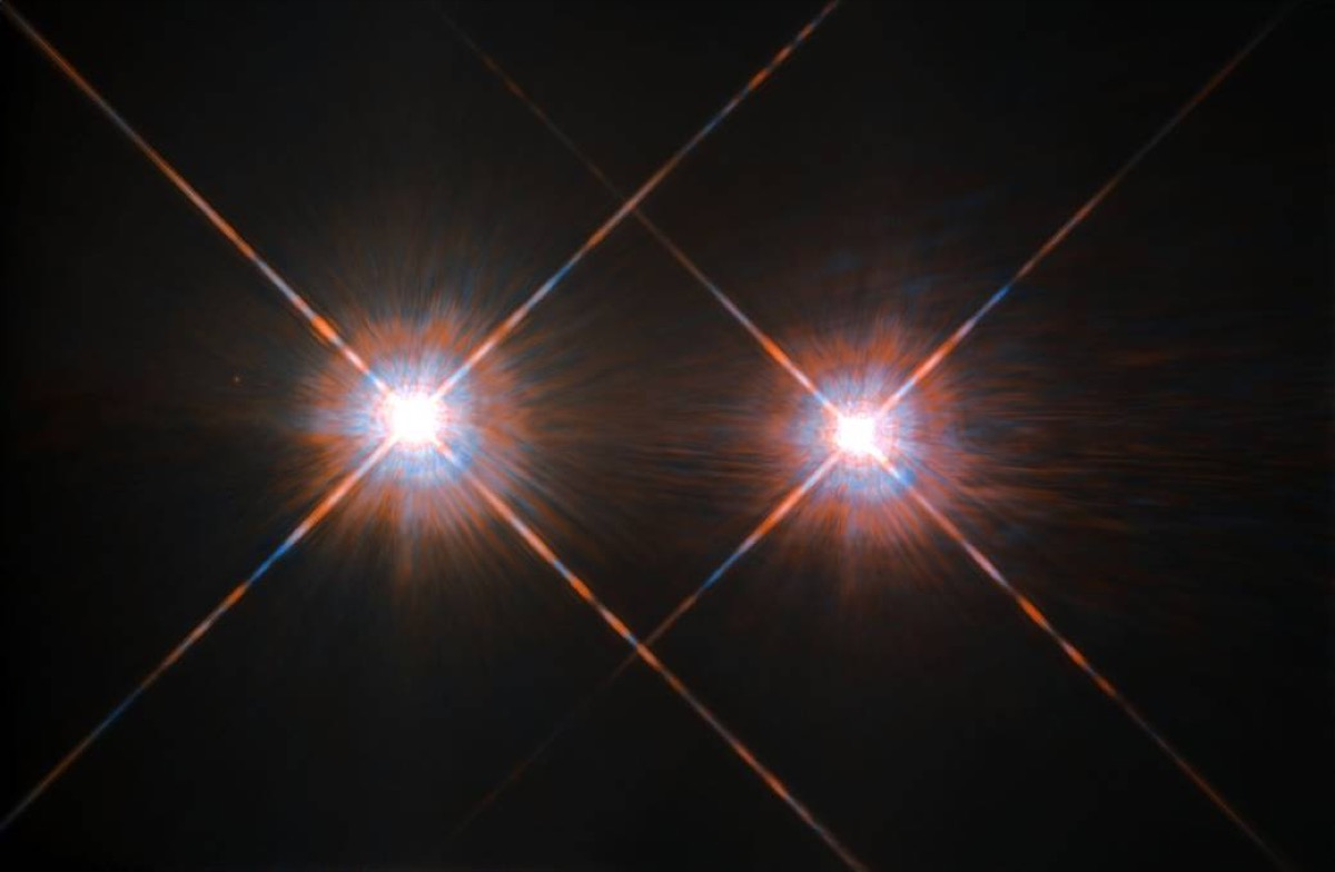 two bright glowing stars on a black background