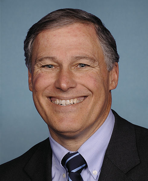 close up portrait of jay inslee grinning against blue background