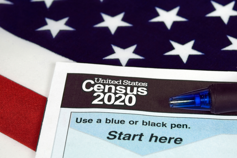 census form on top of american flag. form says 'united states census 2020. use a blue or black pen. start here.'