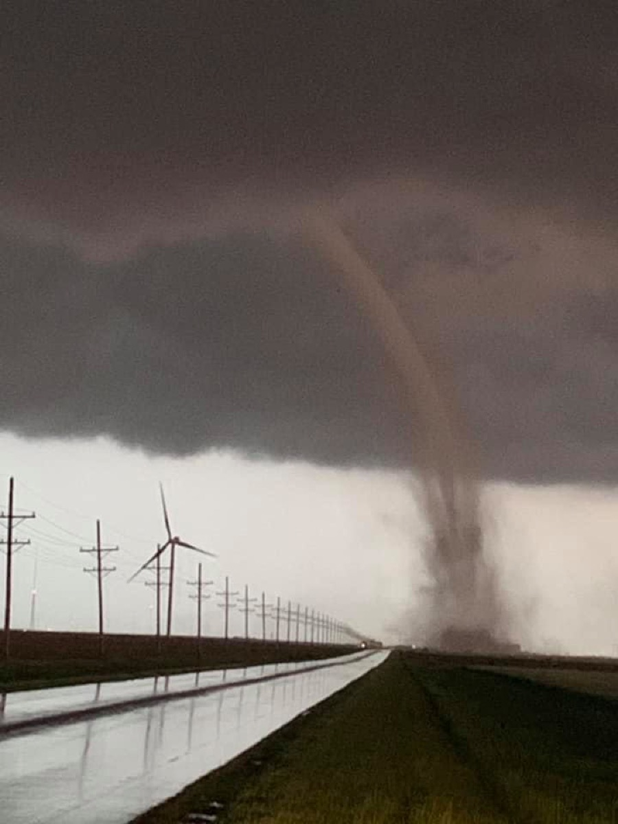 a tornado touching down next to a rural road, with a modern windmill