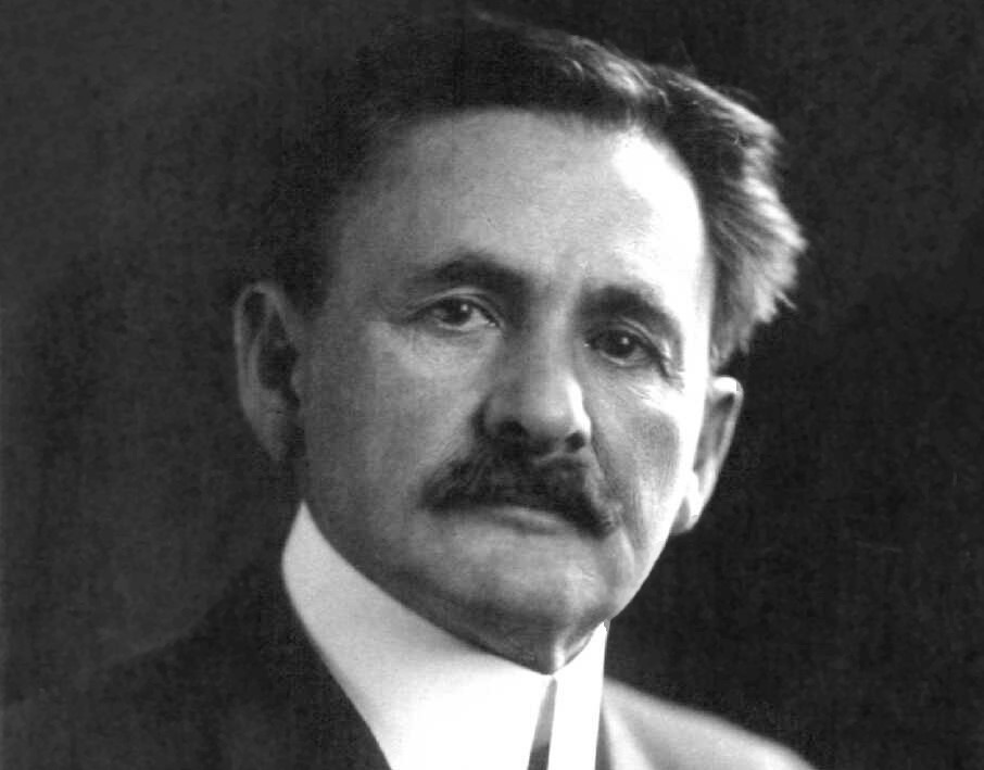 a black and white photo of a white older man with a thick mustache