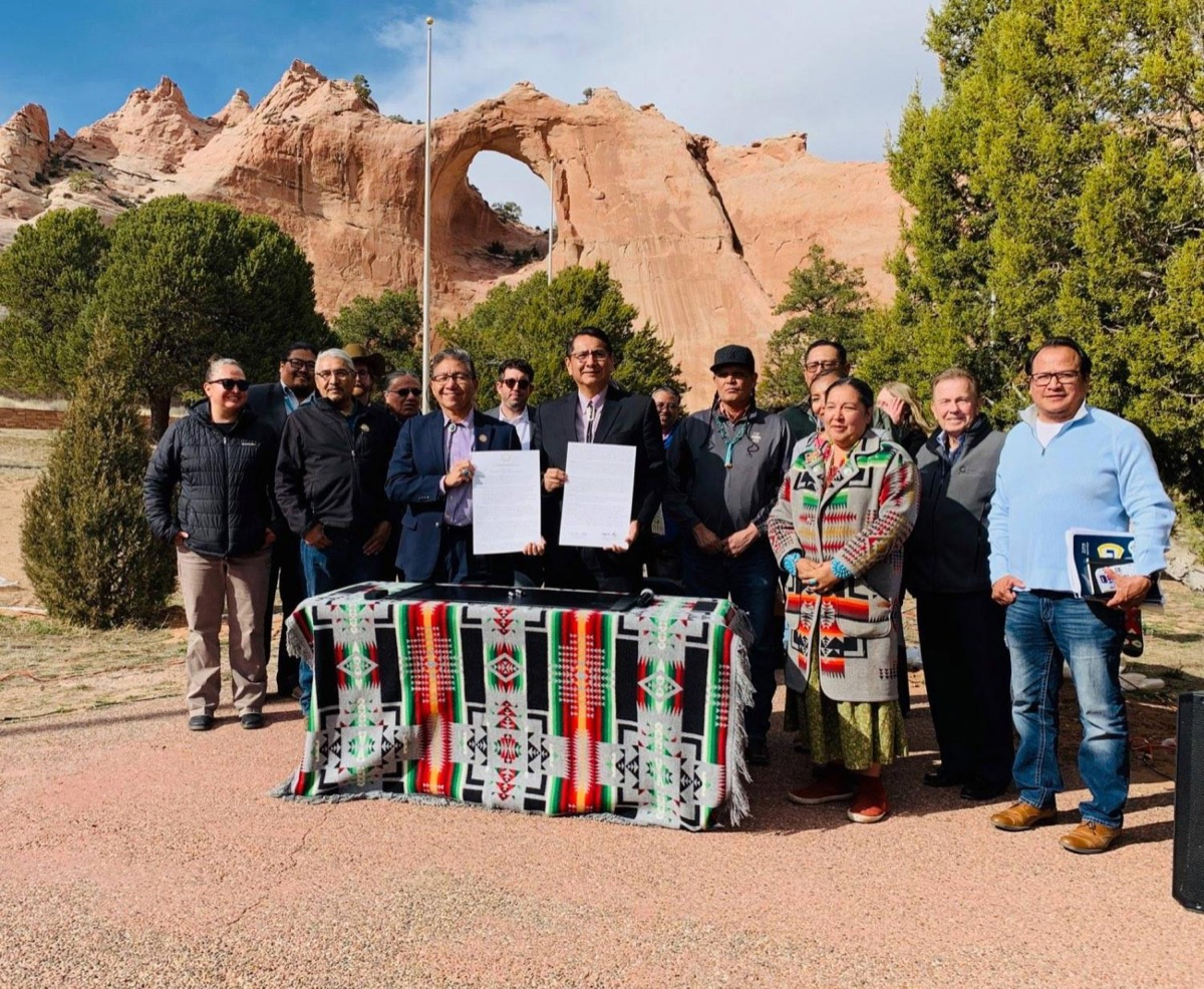 a group of people from the navajo nation standing outside in front of a beautiful red, orange natural sandstone archway. two men in the center hold up signed papers. they are standing behind a table