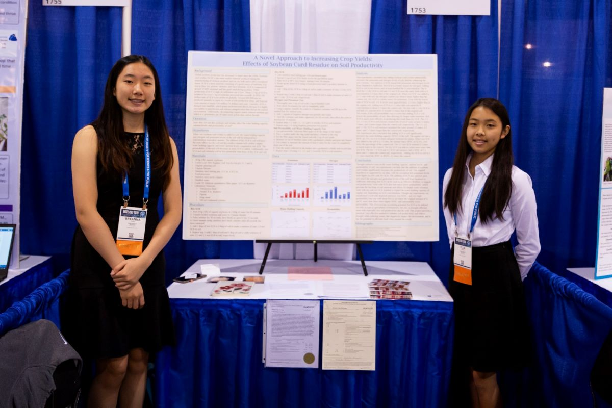 two asian students in front of a science board project. the student on the left is wearing a black dress and the student on the right is wearing a white shirt and skirt