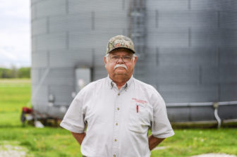 a farmer stands in front of a large silo looking into the camera