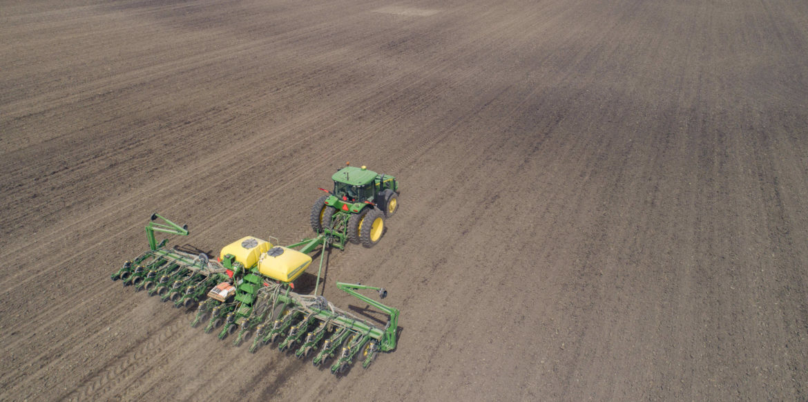 a tractor with a large and wide till travels across a dirt field