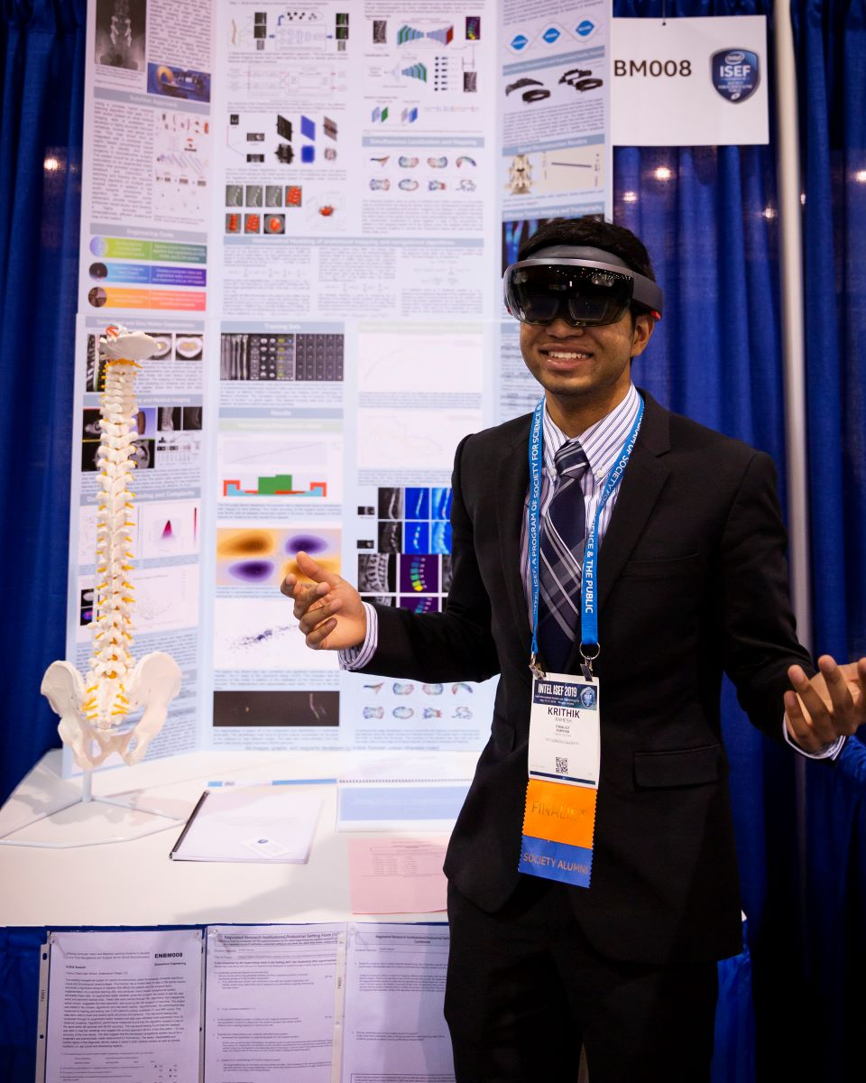 a young student in a suit and tie smiling while wearing VR goggles