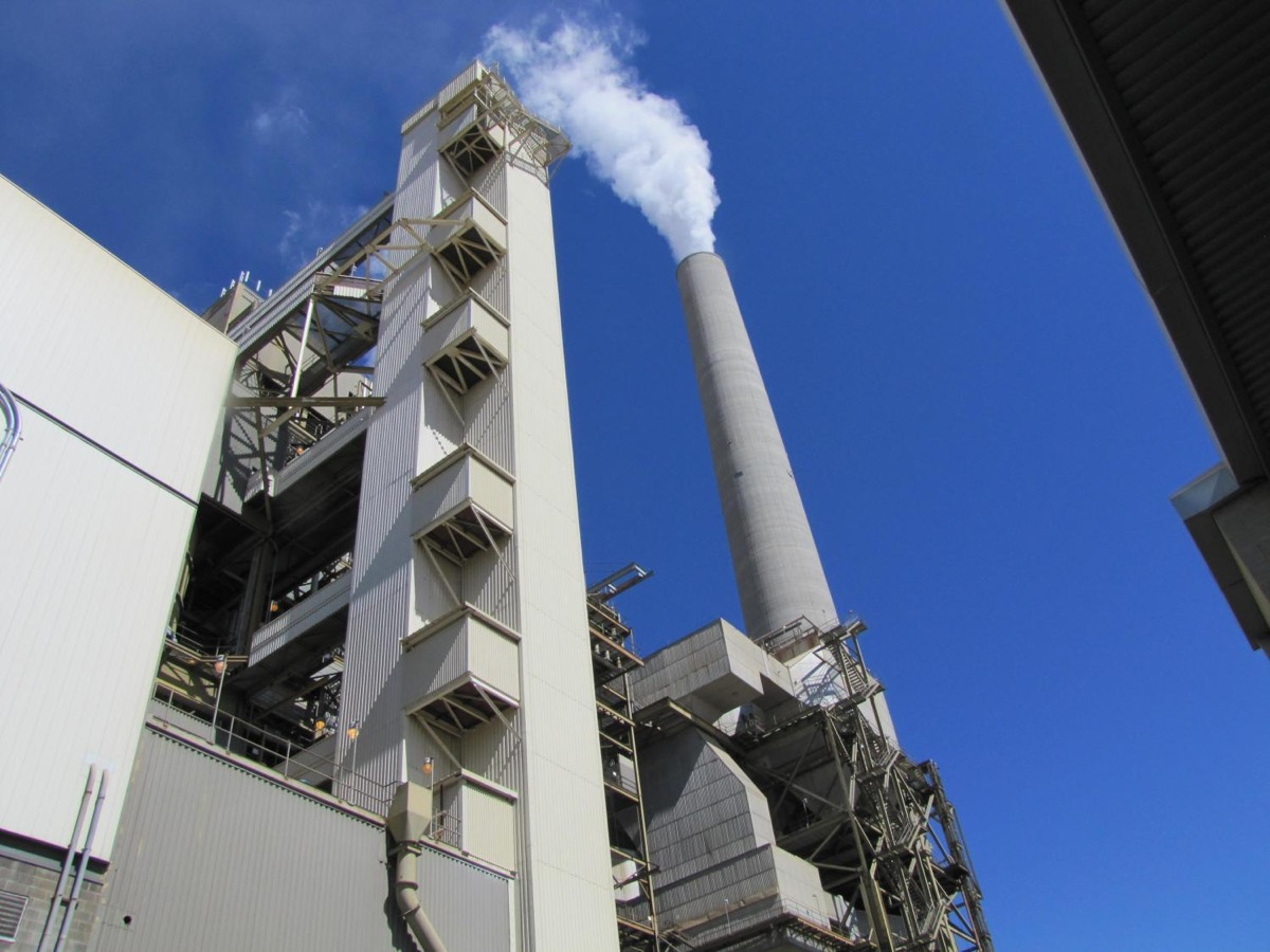 a power plant, with a giant tall smoke stack