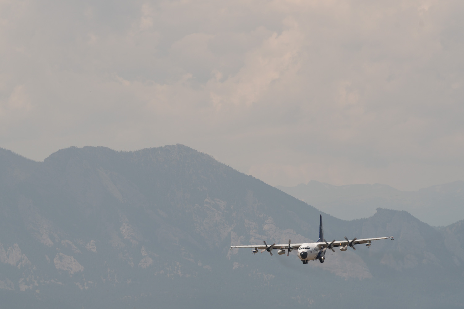 a large propellor plane against the backdrop of smoky mountains