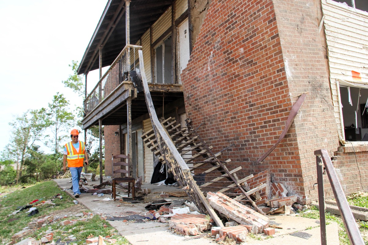 An engineer walks alongside a building where the brick siding has separated from the wall. a staircase has also fallen