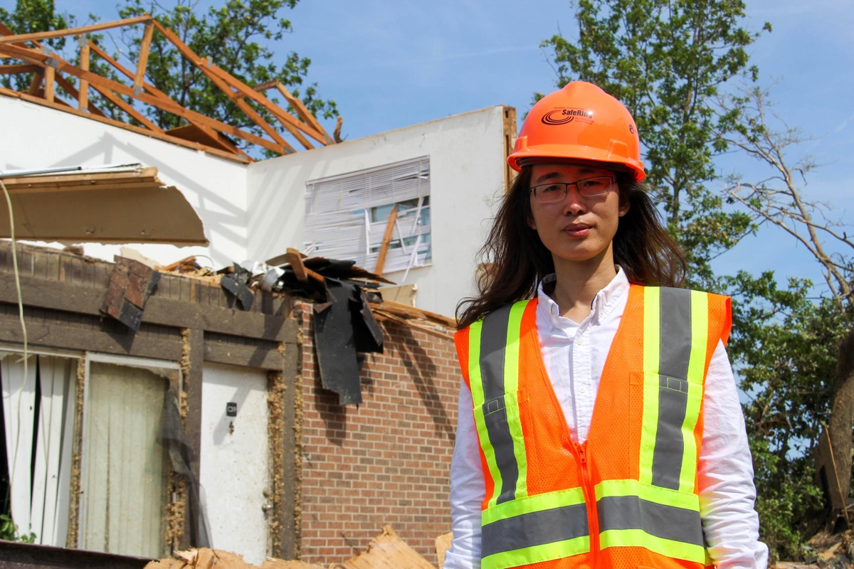 a woman in a hard hat stands in front of a tornado-damaged house