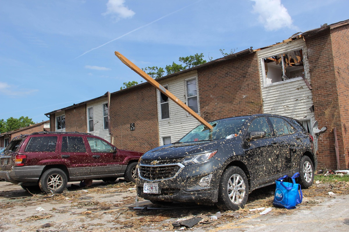 Cars in front of a damaged apartment building. both cars are covered in mud. a 2 by 4 wood beam has gone through the windshield of one car.