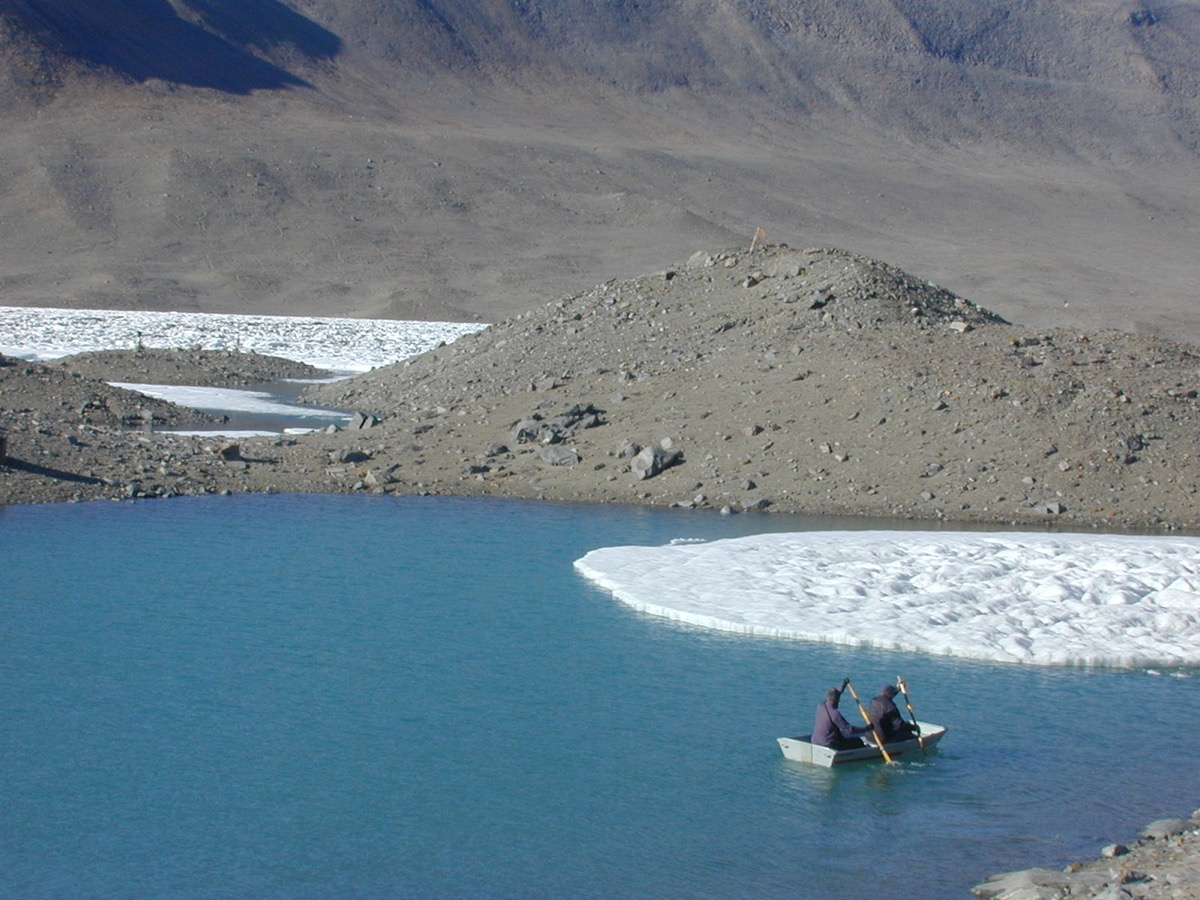 a large blue lake with some bits of snow near by but mostly barren rock. two people sit in a row boat