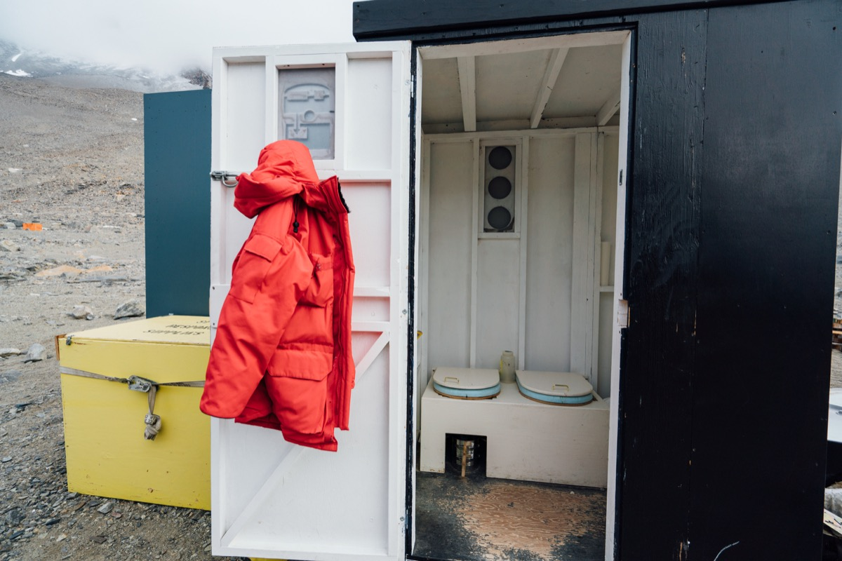 a port-o-john shed with the door open and a big puffy red coat hanging on it