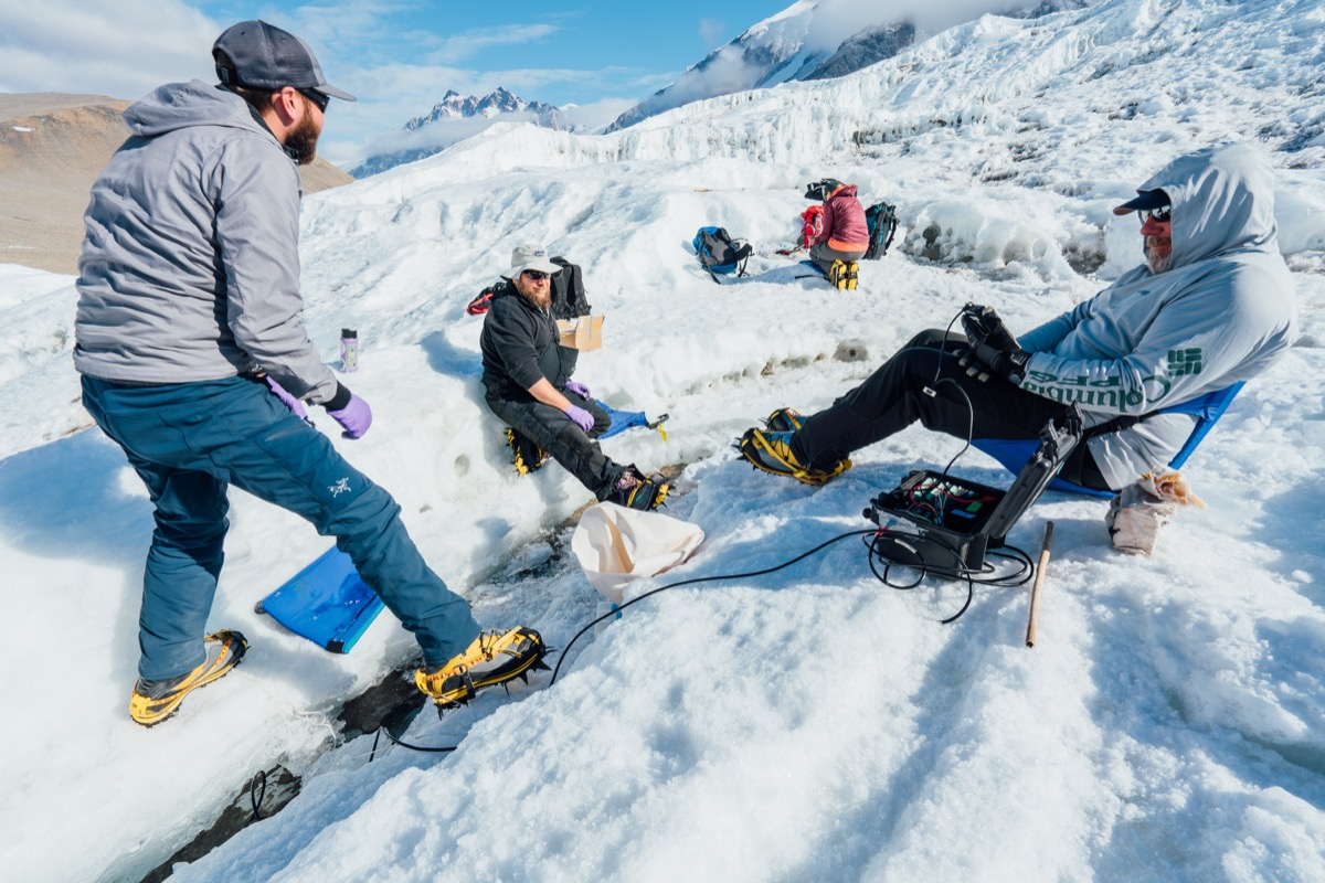 three research scientists gather together on a glacier collecting data