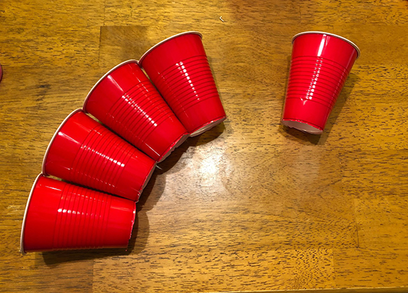 four cups taped together, with the bottom edges touching together so that it looks like the row of cups is creating an arched bridge