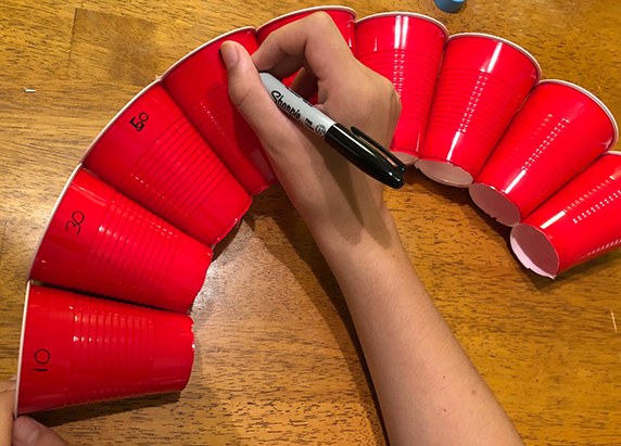 eight cups are taped together, creating a nice curve. a person begins to write in sharpie different numbers on the cups