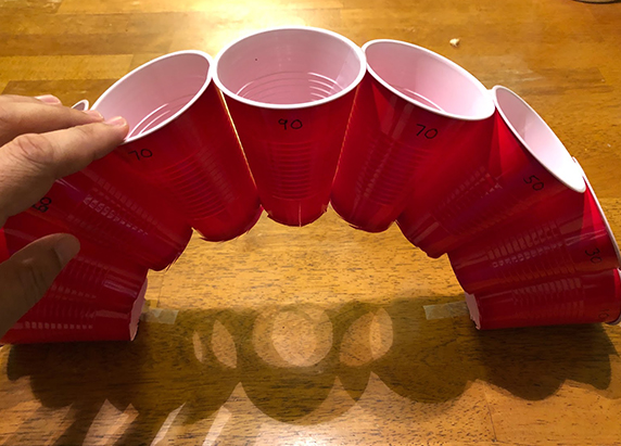 the arch of cups are propped upward on a table to create a bridge like structure