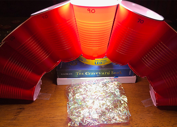 crumpled up foil is placed beneath the arch of cups with the light still shining through the middle highest cup