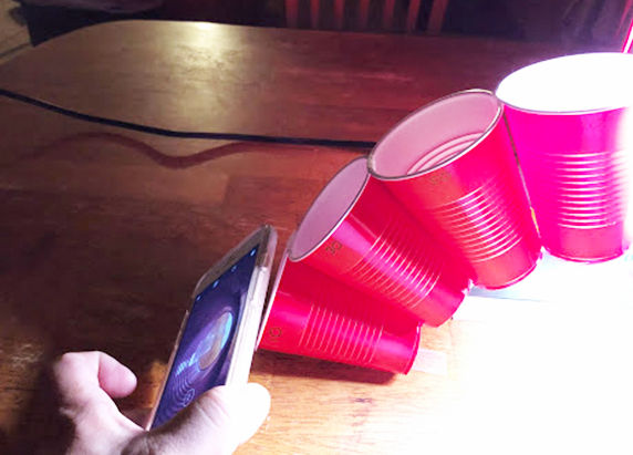 on the left side of the arch, the person holds a smartphone to the bottom left cup and takes a picture through it