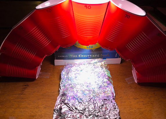 another slightly zoomed out view of the arch of cups, light, and aluminum