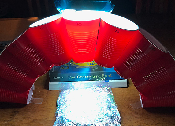 the lamp with the colored cellophane is again placed over the top cup of the arch