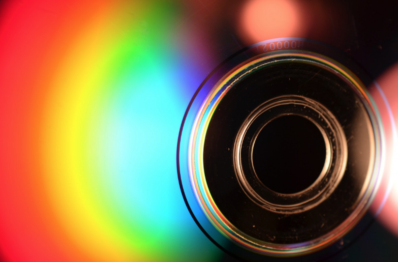 a close up of the bottom of a cd. with light shining on the surface, it shows a rainbow of shiny color