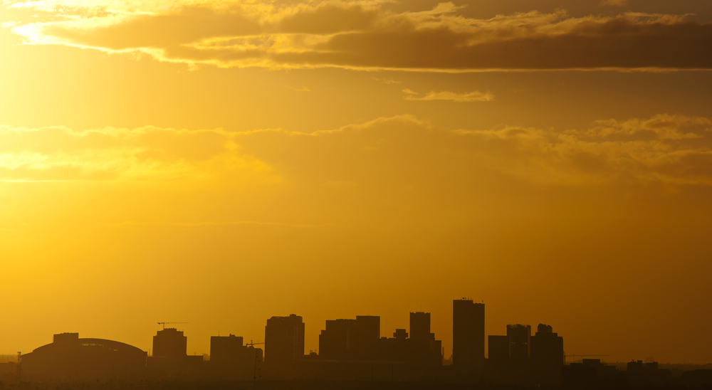 a city skyline under a hazy yellow, brown sunset