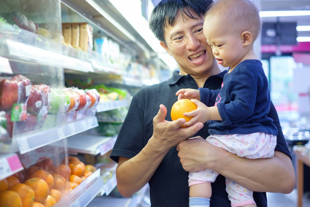 a smiling dad hands his infant an orange in a grocery store