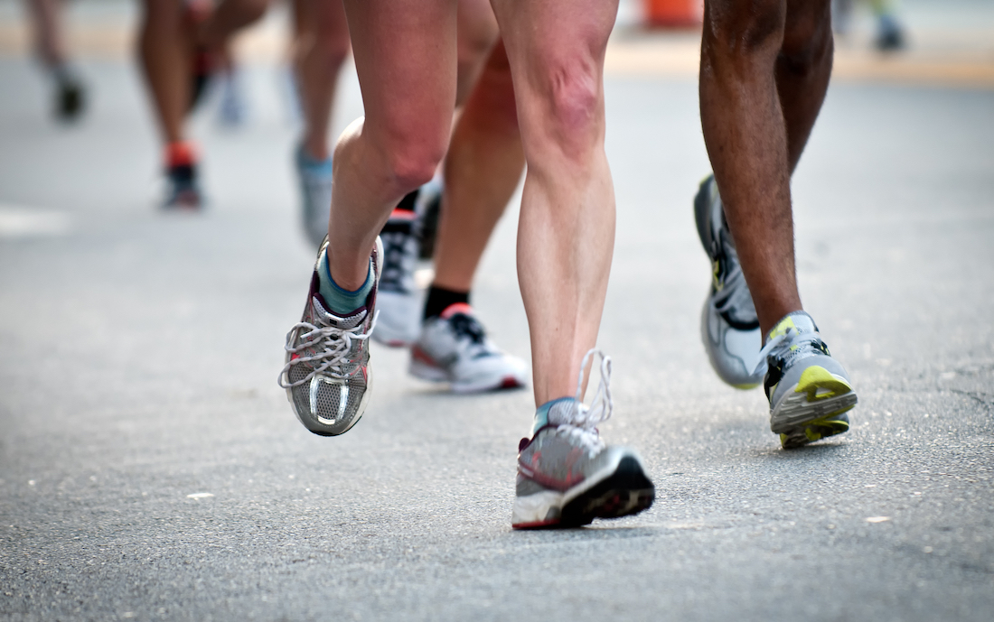 up close image of multiple pairs of legs of men and women and white people and people of color running down a track