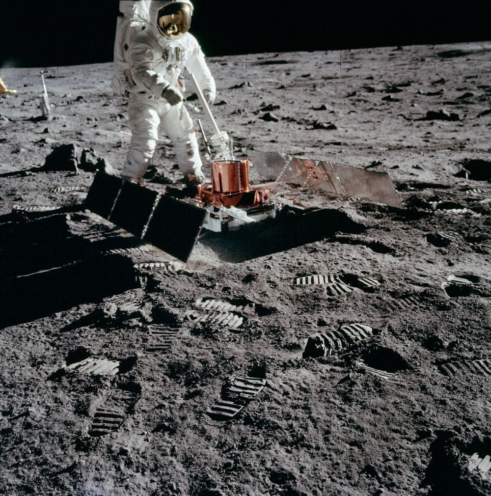 an astronaut uses mechanical equipment on the surface of the moon