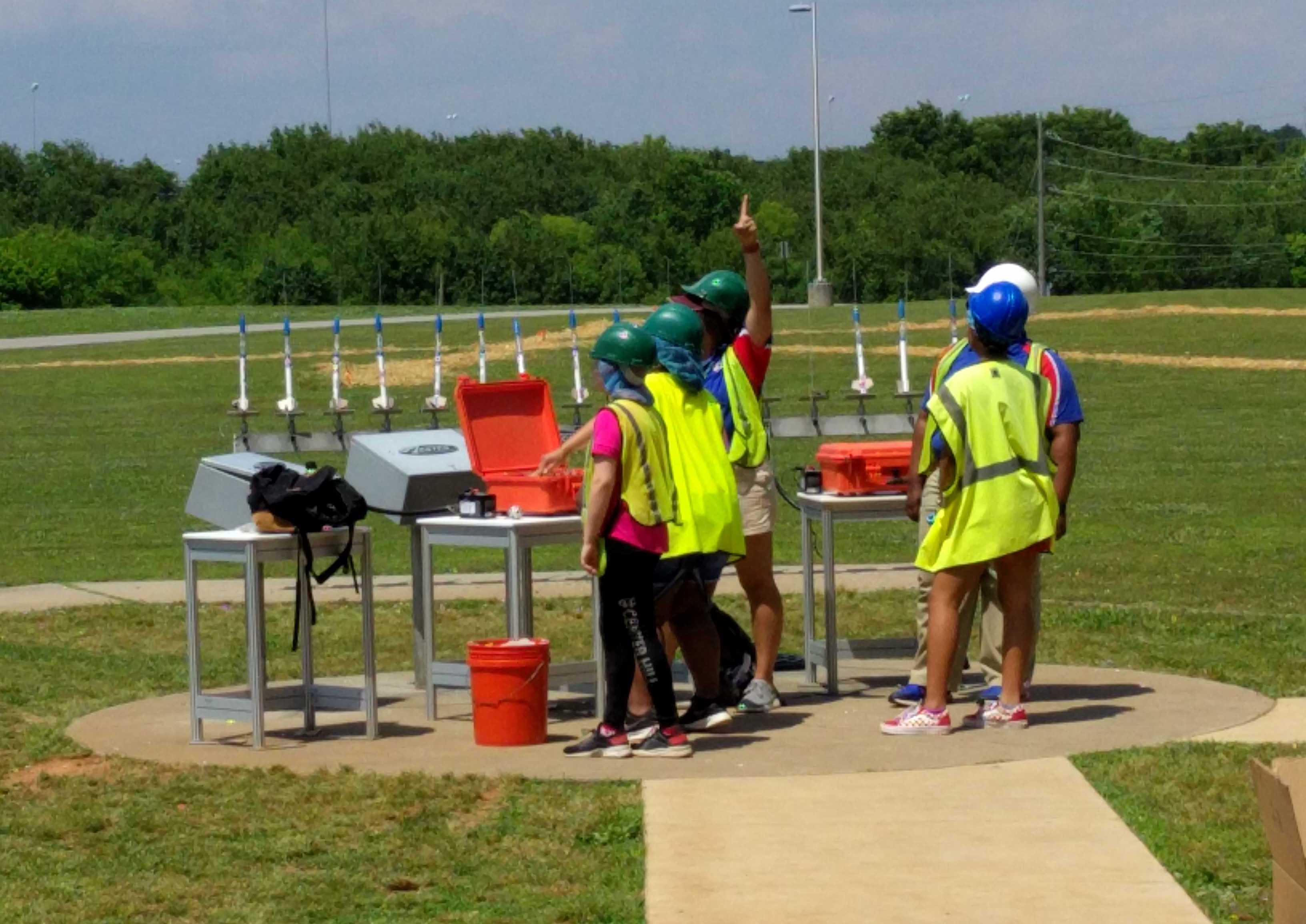 five kids in hard hats and safety vests stand in a grassy field with a row of model rockets