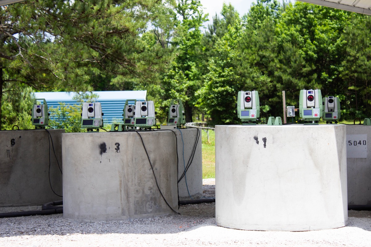 some laser equipment sitting on cement blocks on an outdoor launch facility