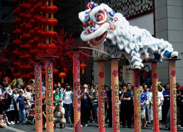 a large traditional white chinese lion puppet in a parade with lots of people
