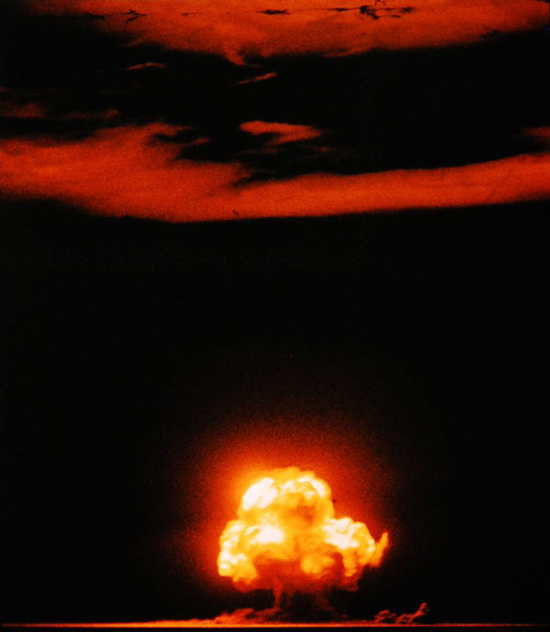 red and yellow mushroom cloud explosion on black background with red streaks across the sky above